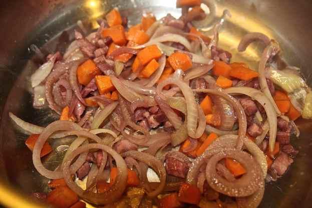 rosolare in una padella antiaderente le cipolle con la pancetta e le carote